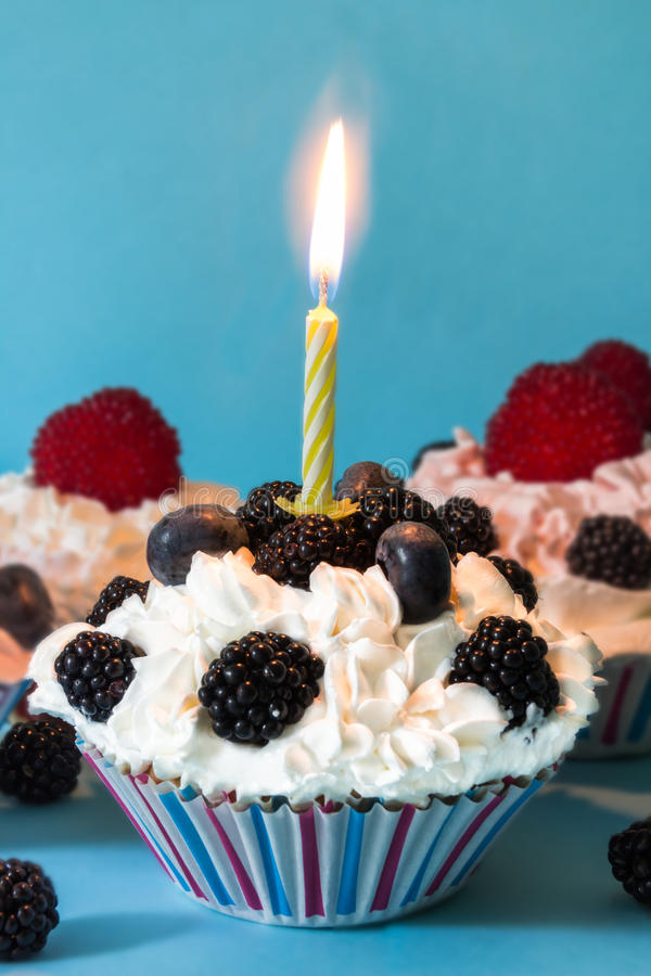 Download CUPCAKES WITH CREAM AND BERRIES, WITH A LIGHTED CANDLE ON BLUE BACKGROUND Stock Photo - Image: 83724878