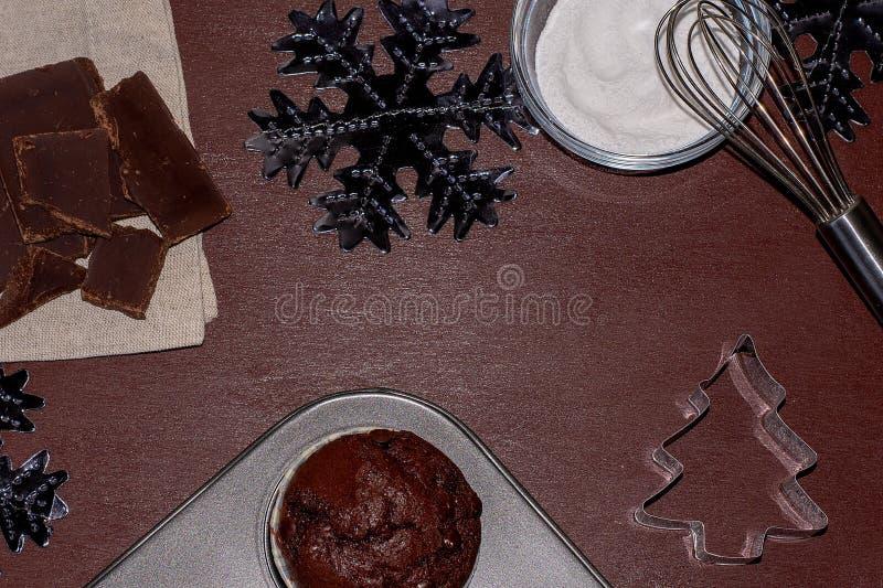Cupcakes en ingrediënten op een donkere achtergrond Bak een cupcake voor Kerstmis royalty-vrije stock afbeelding