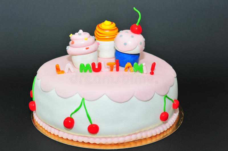 Cupcakes figurines fondant birthday cake. Beautifully crafted fondant cake for a special birthday royalty free stock photo