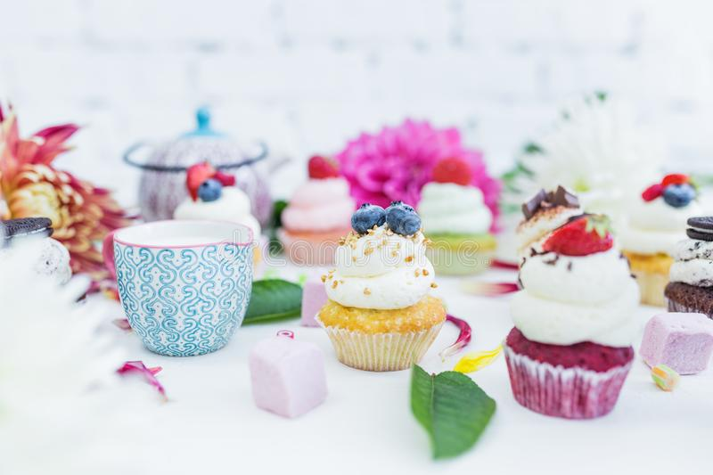 Cupcakes with fresh berries flowers and leaves, a cup of tea or coffee. royalty free stock photography