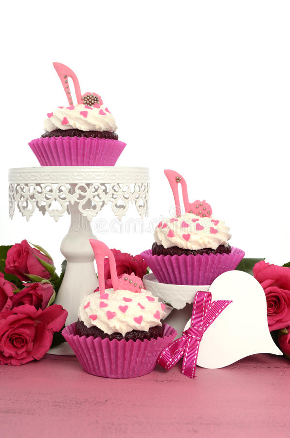 Cupcakes with high heel stiletto fondant shoes. International Womens Day, March 8, cupcakes with high heel stiletto fondant shoes on cake stands on vintage pink royalty free stock photography