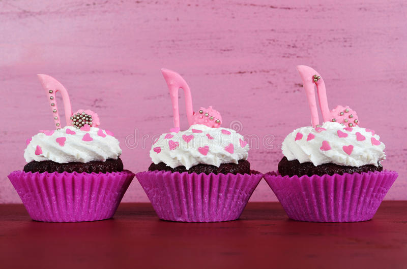 Cupcakes with high heel stiletto fondant shoes. International Womens Day, March 8, cupcakes with high heel stiletto fondant shoes on vintage pink wood background stock photos
