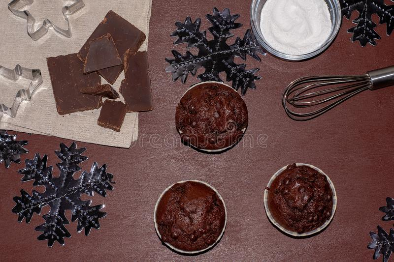 Cupcakes and ingredients on a dark background. Bake a cupcake for christmas stock photo