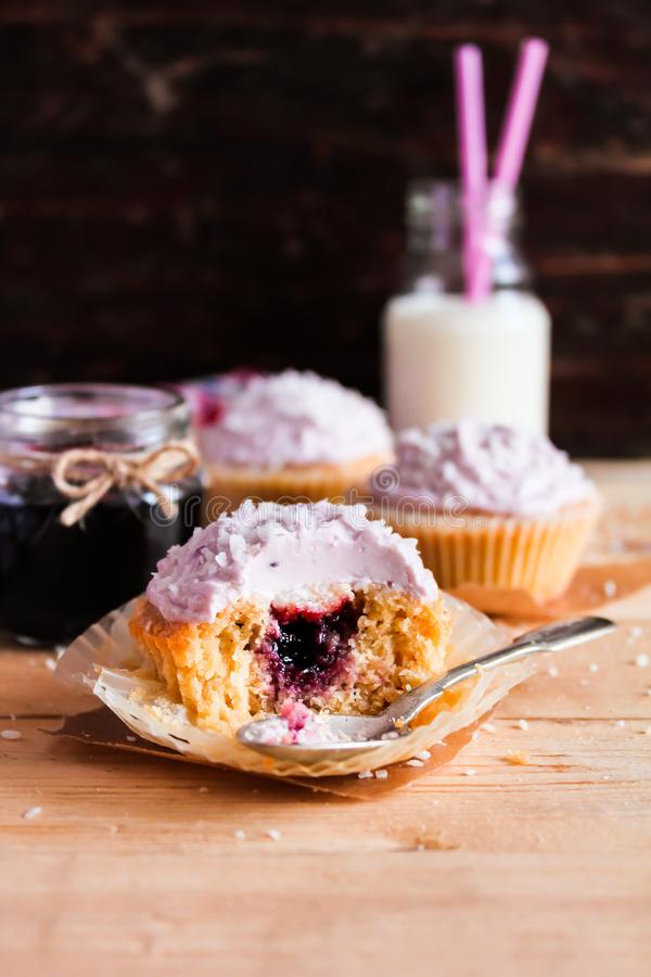 Cupcakes with mascarpone cream cheese, black currant jelly jam and freshly shredded coconut on a wooden table with a bottle of mil stock photography