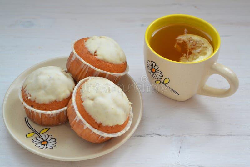 Cupcakes met kop thee, steekt sjofele achtergrond aan stock foto