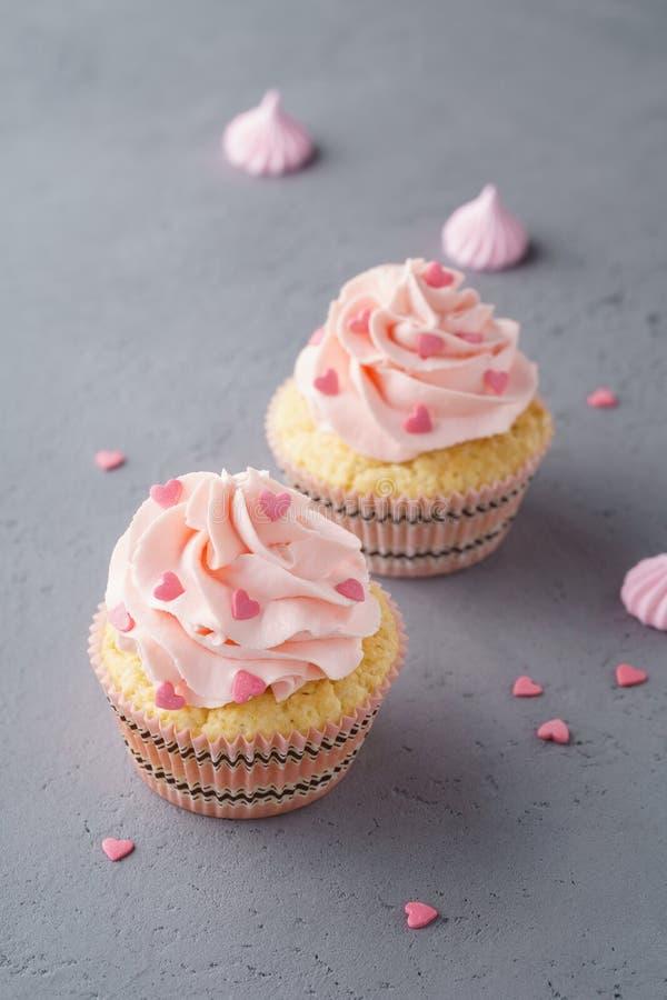 Cupcakes met roze room en hart gevormd suikergoed voor dessert stock afbeelding