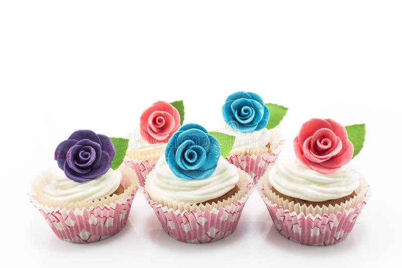 Cupcakes met rozen op een witte achtergrond wordt verfraaid die royalty-vrije stock foto's