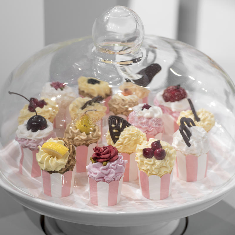 Cupcakes. Pastel cupcakes under glass cover stock image