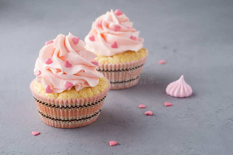Cupcakes with pink cream and heart shaped candy for dessert royalty free stock photography