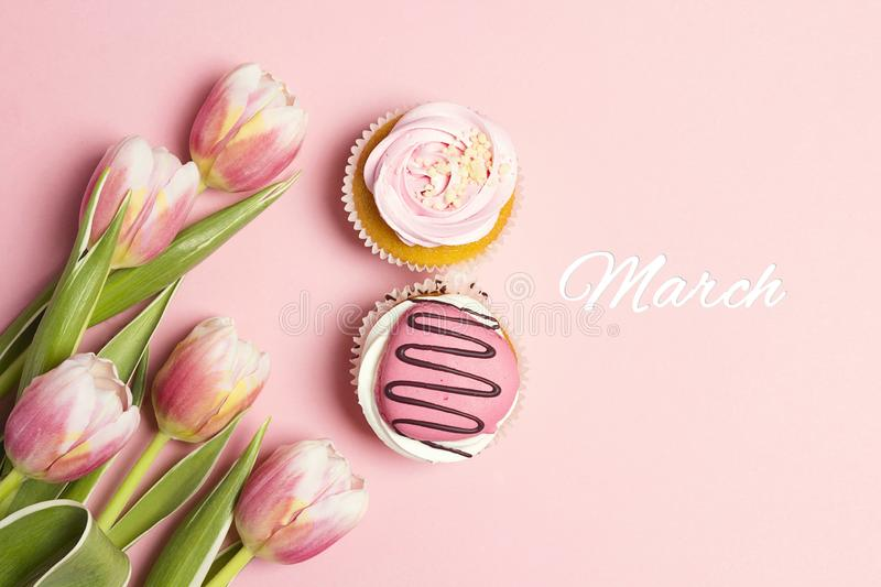Cupcakes in shape of number 8 with tulip flowers on pink pastel background. March 8 stock photography