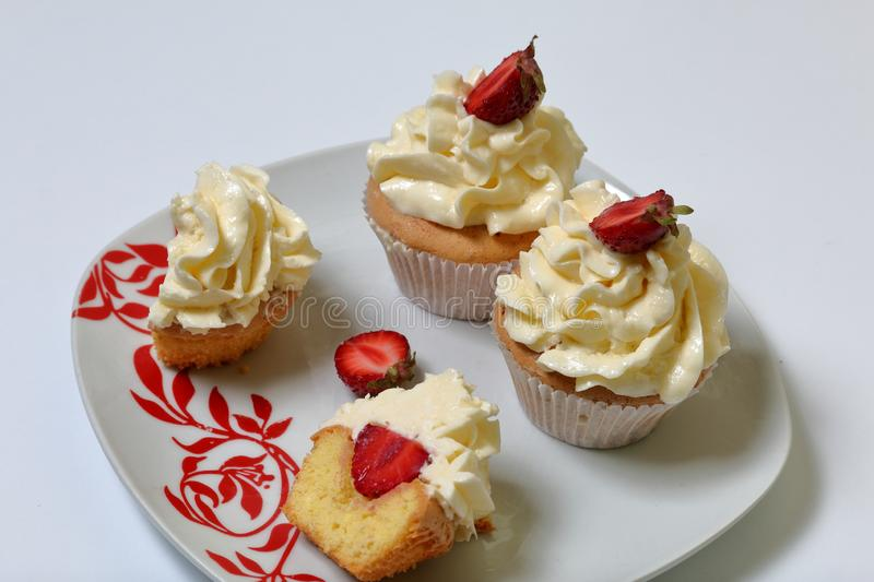 Cupcakes with strawberries and butter cream. stock photos