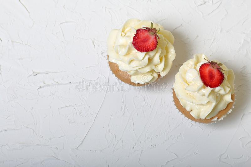 Cupcakes with strawberries and butter cream. royalty free stock photos