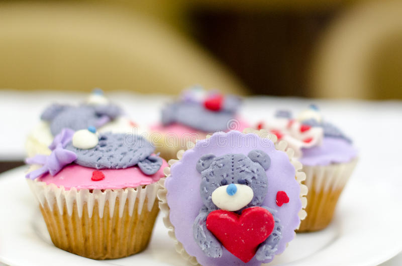 Cupcakes with teddy bear and hearts on white rustic background Valentine`s Day cupcake. Cupcakes with teddy bear and hearts on white rustic background royalty free stock images
