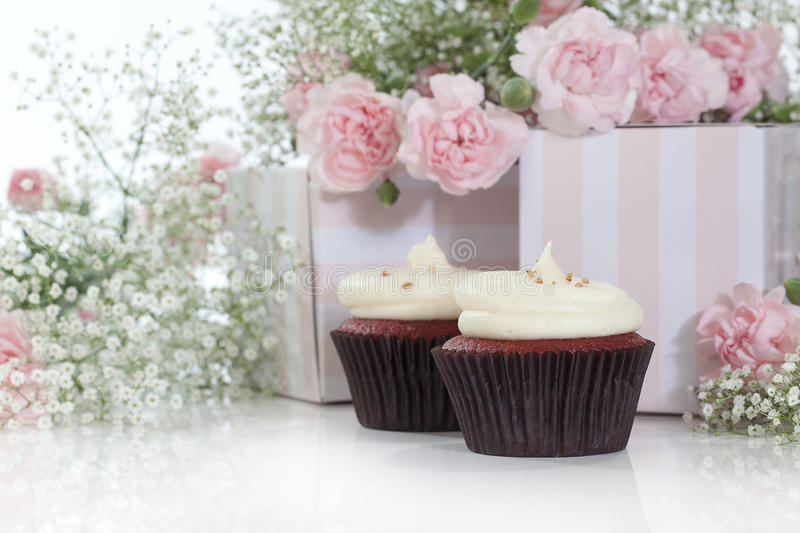 Cupcakes. Two cupcakes with white frosting in front of pink and white striped boxes with pink carnations blurred in background royalty free stock images