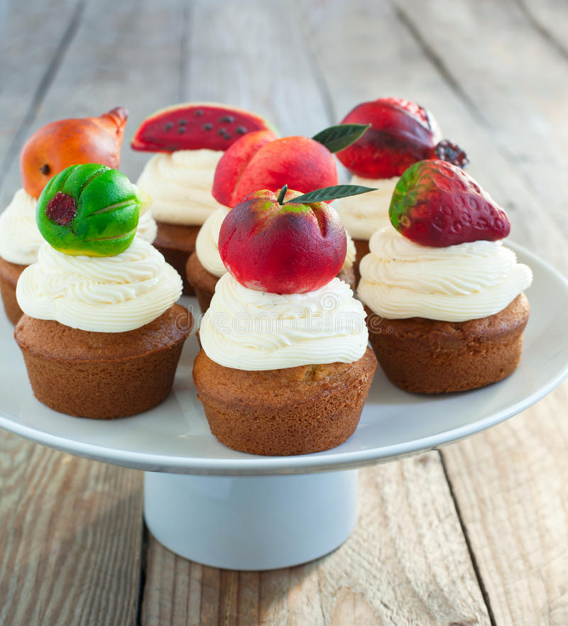 Cupcakes with vanilla buttercream and marzipan fruits. Homemade Cupcakes with vanilla buttercream and marzipan fruits royalty free stock photo