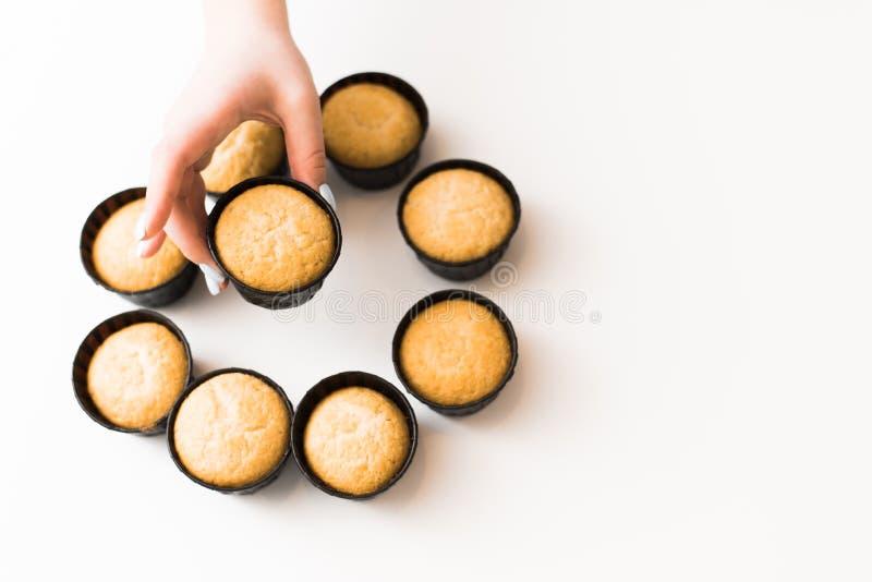 Cupcakes zonder room op een witte achtergrond met een plaats voor de tekst Het meisje neemt een cupcake van een stapel van snoepj royalty-vrije stock fotografie