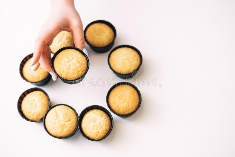 Cupcakes zonder room op een witte achtergrond met een plaats voor de tekst Het meisje neemt een cupcake van een stapel van snoepj royalty-vrije stock foto