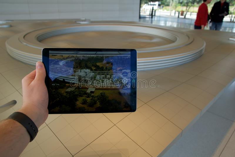 CUPERTINO, CALIFORNIA, UNITED STATES - NOV 26th, 2018: People at the Apple Park Visitor Center in Silicon Valley explore. The new Apple Offices using a scaled royalty free stock photos