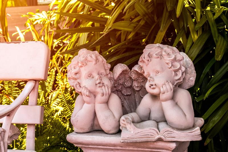 Cupid and Angel statue, Boy and girl statue in garden stock photography