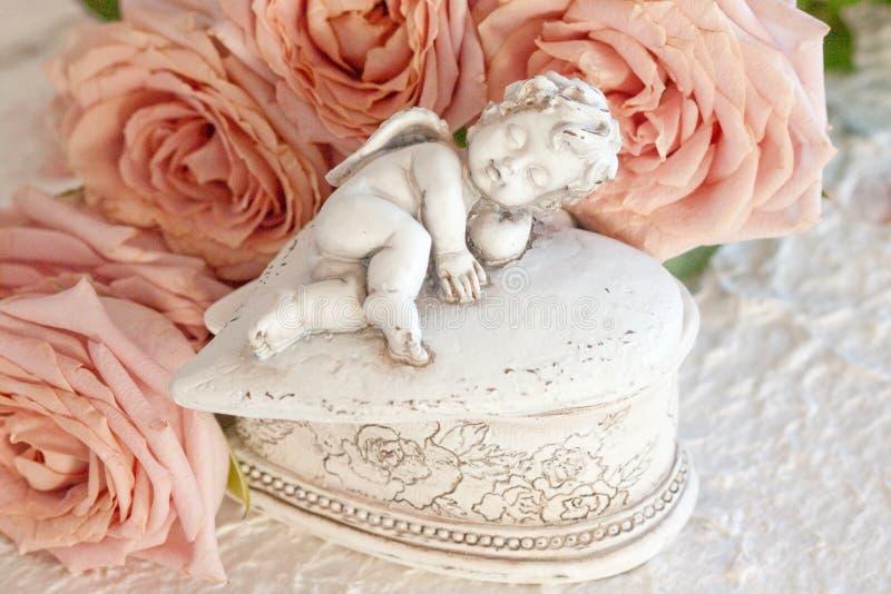 Cupid con le rose dentellare fotografia stock