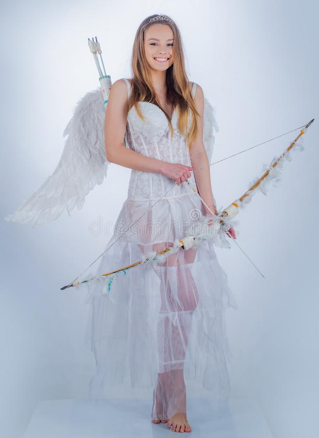 Cupid girl aiming at someone with an arrow of love. Girl dressed as an angel on a light background. Love concept. Angel royalty free stock image