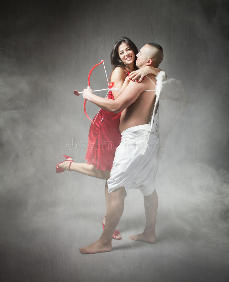 Cupid with girl in red dress royalty free stock photo