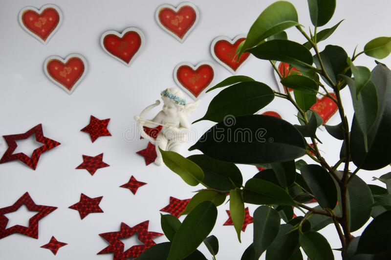Cupid hid behind ficus leaves and aims an arrow at another heart stock photography