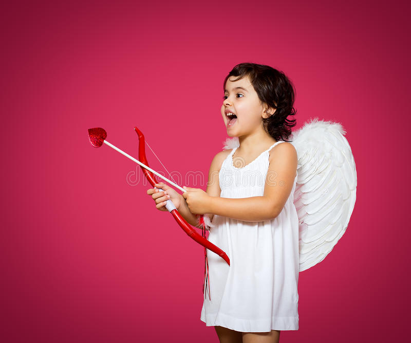 Cupid little girl. With a bow, arrow and wings stock image