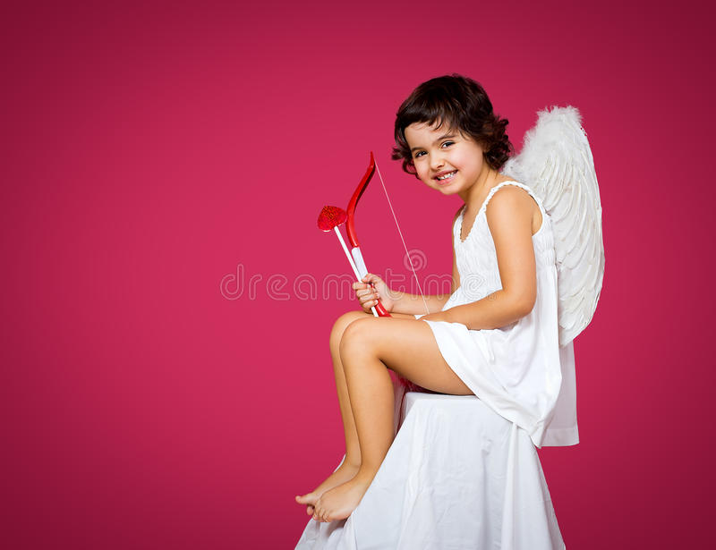 Cupid little girl. With a bow, arrow and wings stock images