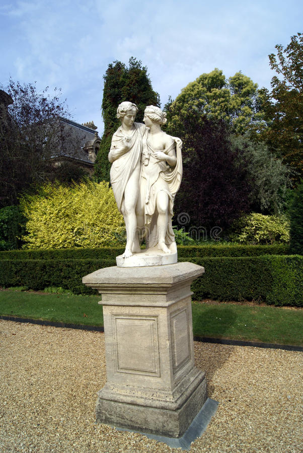 Cupid and Psyche lovers statues on a pedestal. Garden decoration of marble statues of lovers on a pedestal stock photography