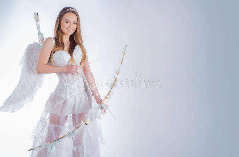 Cupid in valentine day. Real fairy from magical stories. Pretty white little girl as the cupid with a bow and arrow royalty free stock photo