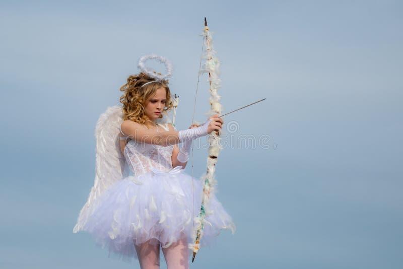 Cupido adolescente lindo en la nube - fondo del cielo Rose roja Ni?o encantador Concepto de Daygirl de las tarjetas del día de Sa fotos de archivo libres de regalías