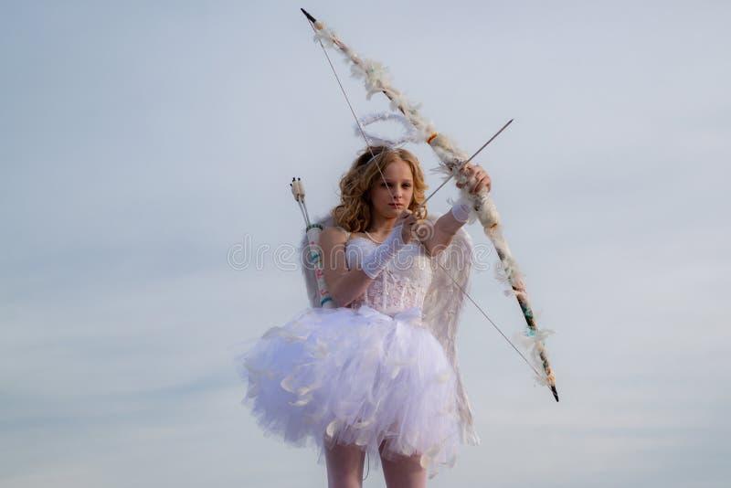 Cupidon de l'adolescence mignon sur le nuage - fond de ciel Belle et mignonne jeunesse Le beau cupidon de fille avec le tir ? l'a photo stock
