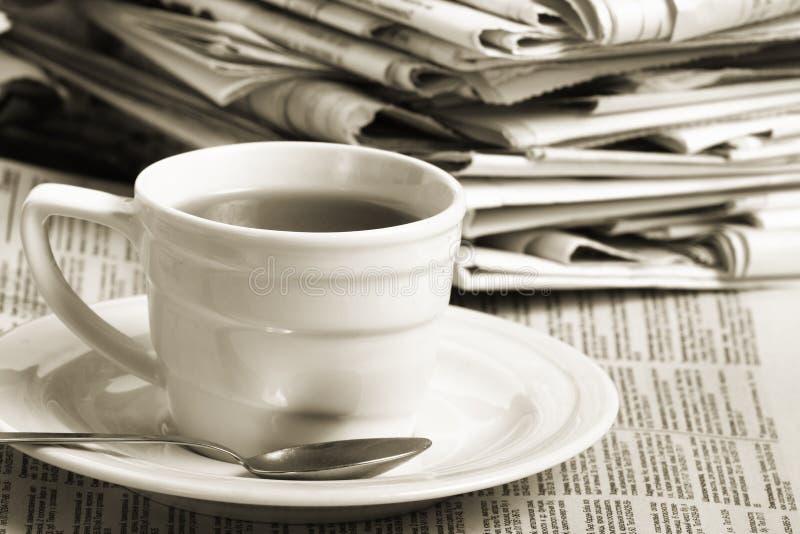 Cupkaffee auf Wirtschaftsnachrichten stockfotografie