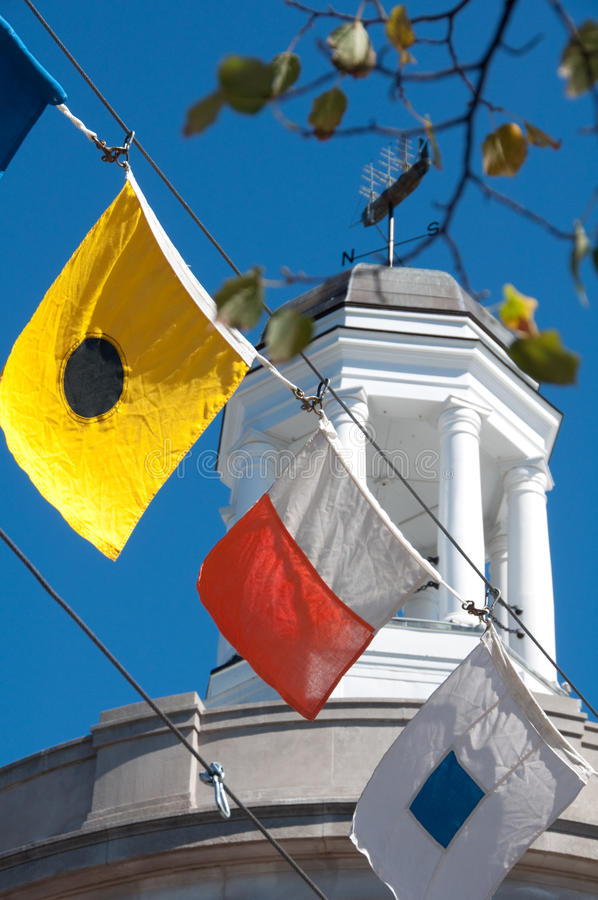 Cupola and Flags in Downtown Bath, Maine. Nautical flags hang in a stream across Main Street in front of the city hall in Bath, Maine stock photos