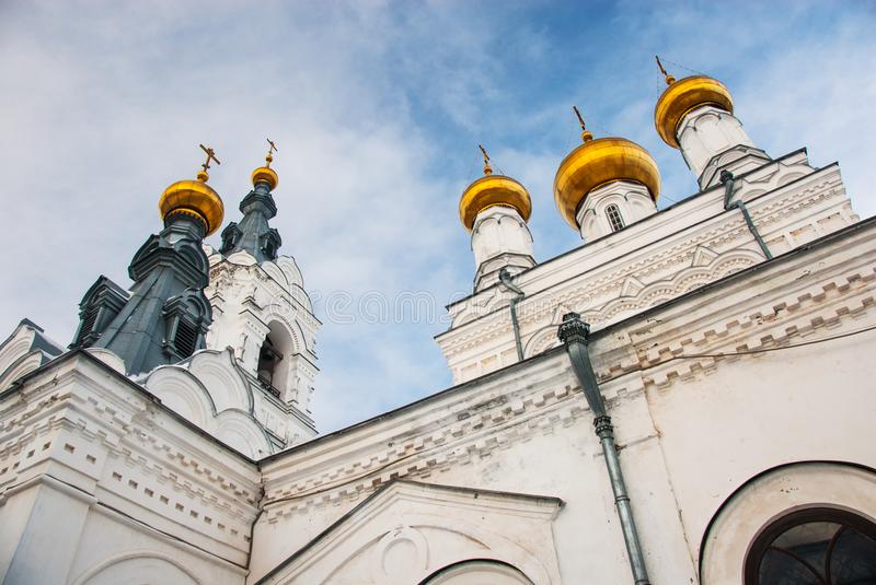 Cupolas and towers of old Orthodox cathedral. Golden cupolas, walls and towersof old ancient cathedral on the sky background stock photo
