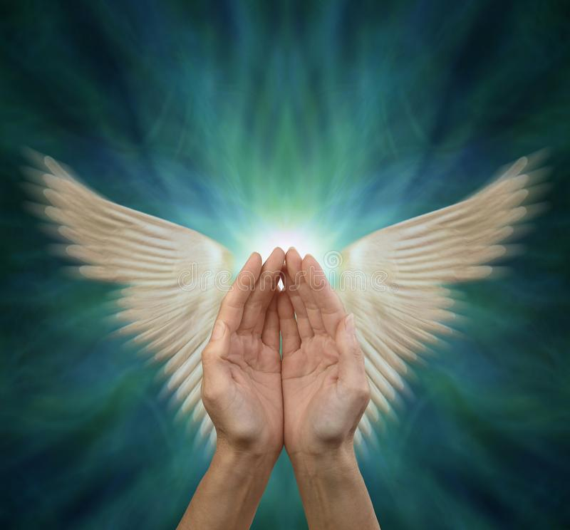 Sending out Angelic Healing Energy. Cupped female hands with motion blurred angel wings either side on a blue green background with copy space above royalty free stock photography