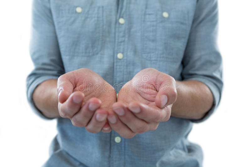 Cupped hands of man pretending to hold an invisible object. Against white background royalty free stock photography