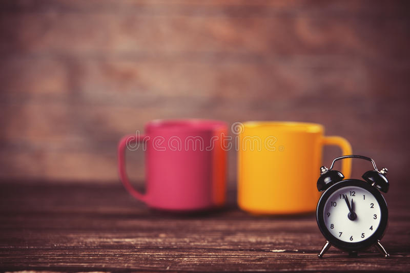 Cups and alarm clock. Two tea cup and alarm clock on wooden table stock photos