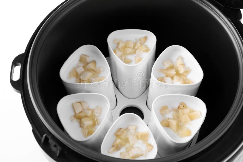 Cups of banana yogurt in multi cooker royalty free stock photo