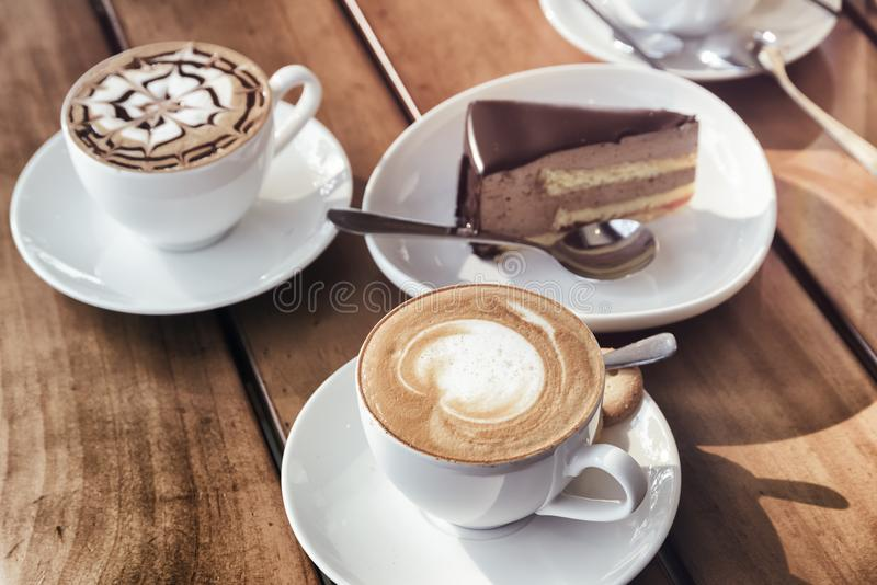 Cups of Cappuccino coffee and chocolate mousse cake. Toned image stock photos
