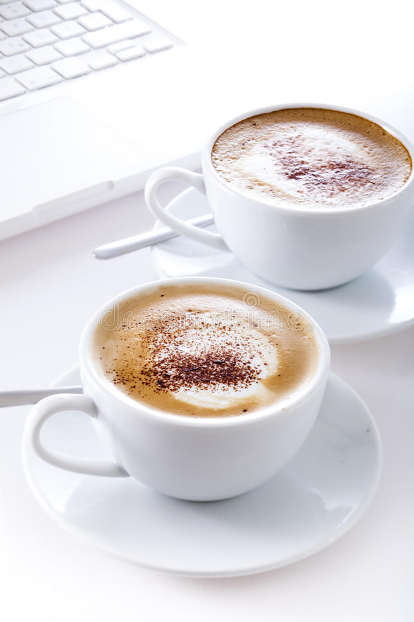 Cups of cappuccino with laptop royalty free stock photography