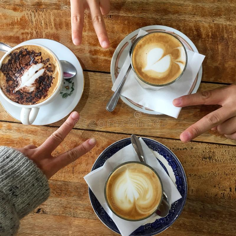 Cups of cappuccino and v signs stock photography