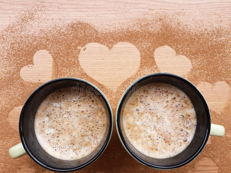 Cups of cappucino on wooden background royalty free stock images