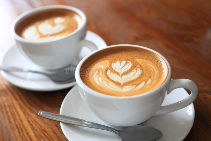 Two cups of coffee latte art with tulip pattern on wooden table with copy space stock photography