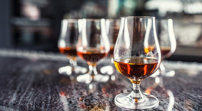 Cups with a cognac rum brandy or whiskey drink. royalty free stock images