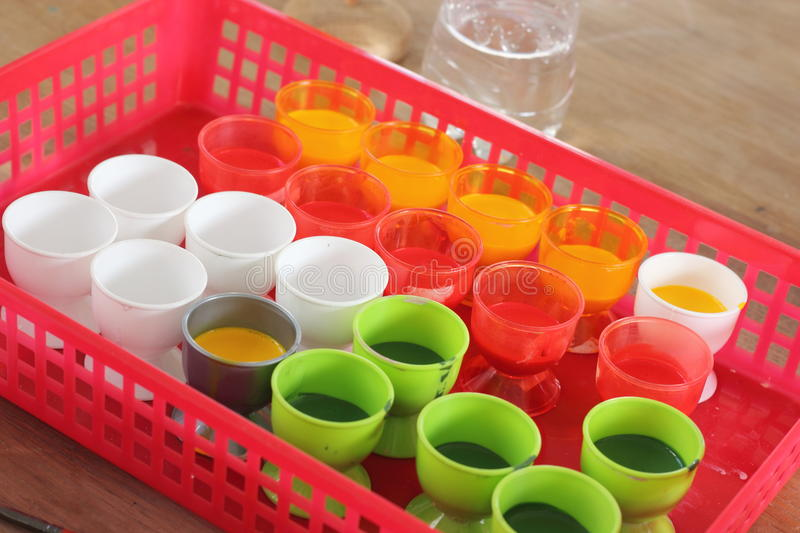 Cups with colorful paint stock images