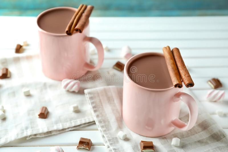 Cups of delicious cocoa and sweets on white table stock photo