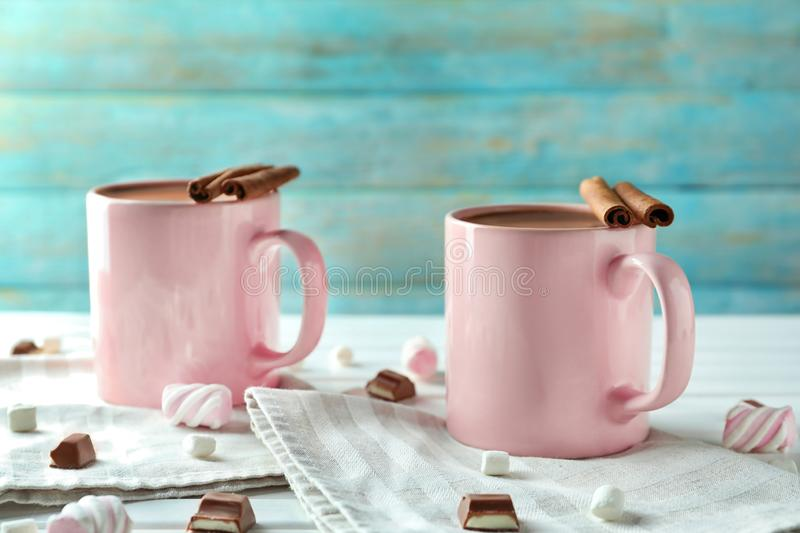 Cups of delicious cocoa and sweets on white table royalty free stock photo