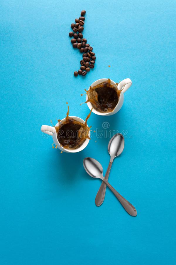 Cups with espresso splash, saucers, teaspoon and coffee beans on blue paper background. Good morning concept. Art food style royalty free stock image